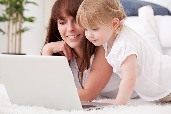 Happy young mother and her daughter using a laptop on Photodune
