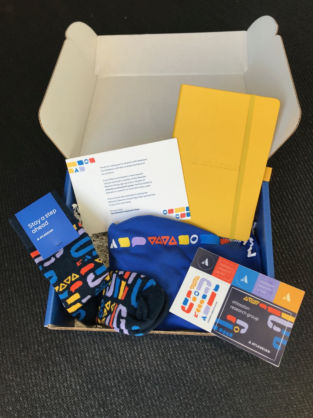 Box with branded, socks, t-shirt, stickers, and notebook