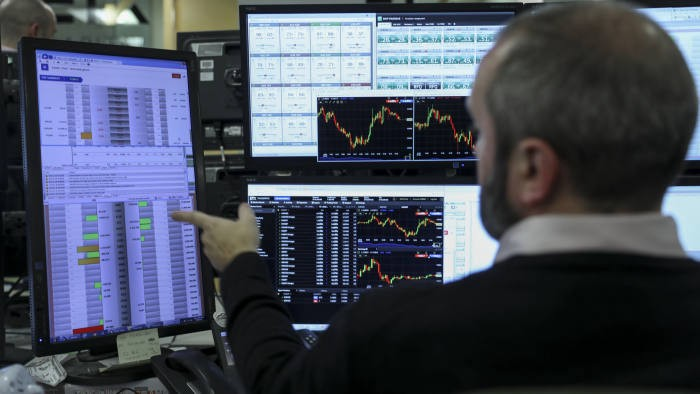 Man uses financial trading software to monitor stocks patterns.