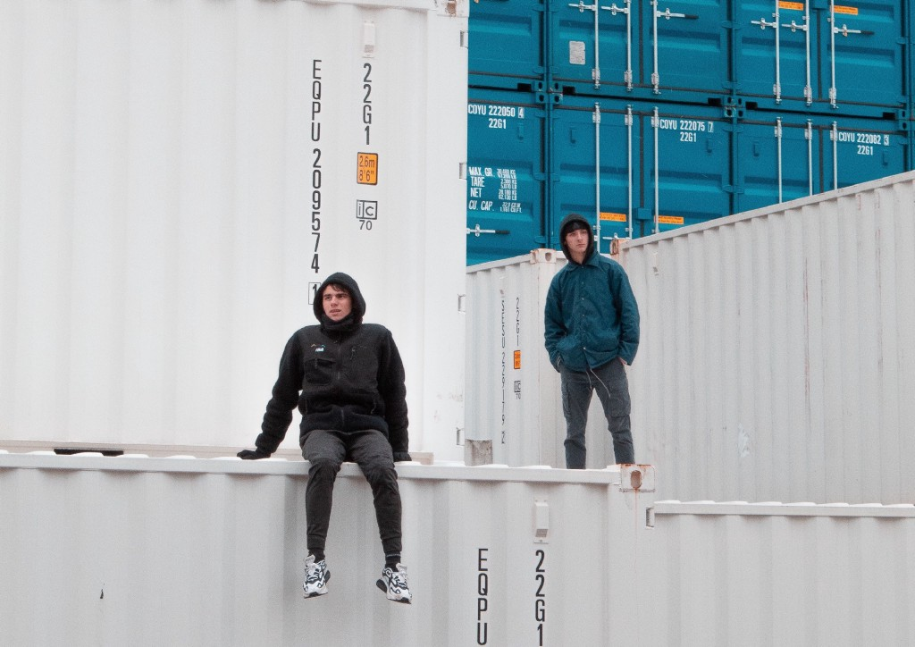 Two guys in hoodies standing on containers